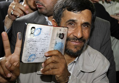President Mahmoud Ahmadinejad holds his passport while flashing the victory sign after casting his ballot for the Iranian presidential election in Tehran.